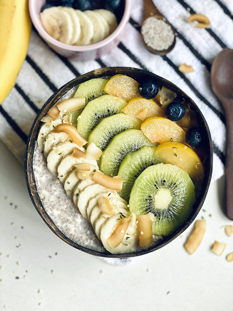 Healthy and nutritious snack or meal topped with mixed fruits - banana, kiwi, peach blueberry and peanuts. PIXERF.