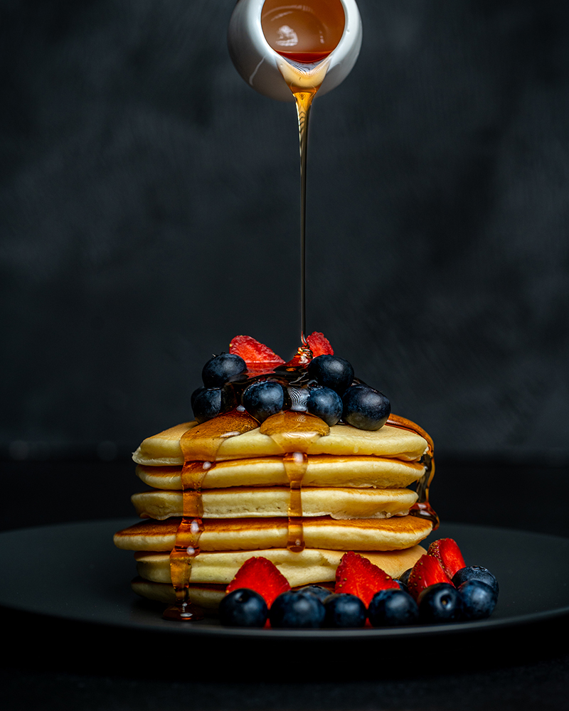 Pouring honey over a stack of delicious blueberry and strawberry pancake dessert. PIXERF