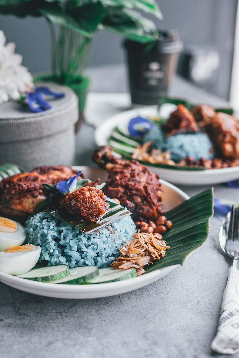 Taditional Nasi Lemak with chicken wings and drumsticks, egg, fried anchovies (ikan bilis) and chilli served in white ceramic plates. PIXERF.