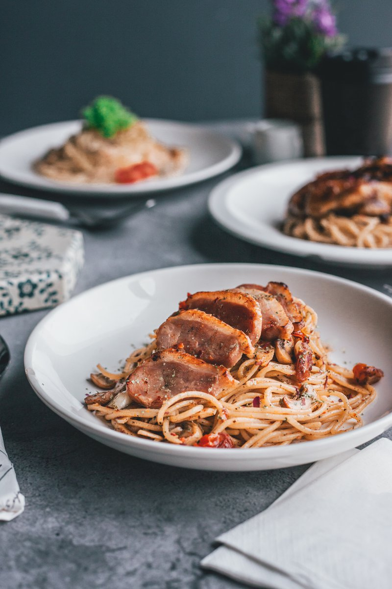 Three servings of tasty western chicken and smoked duck aglio olio pasta served on white ceremic plates. PIXERF