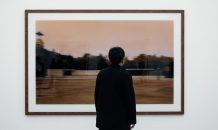 Shot from the back, a man is seen admiring a framed artwork at a gallery