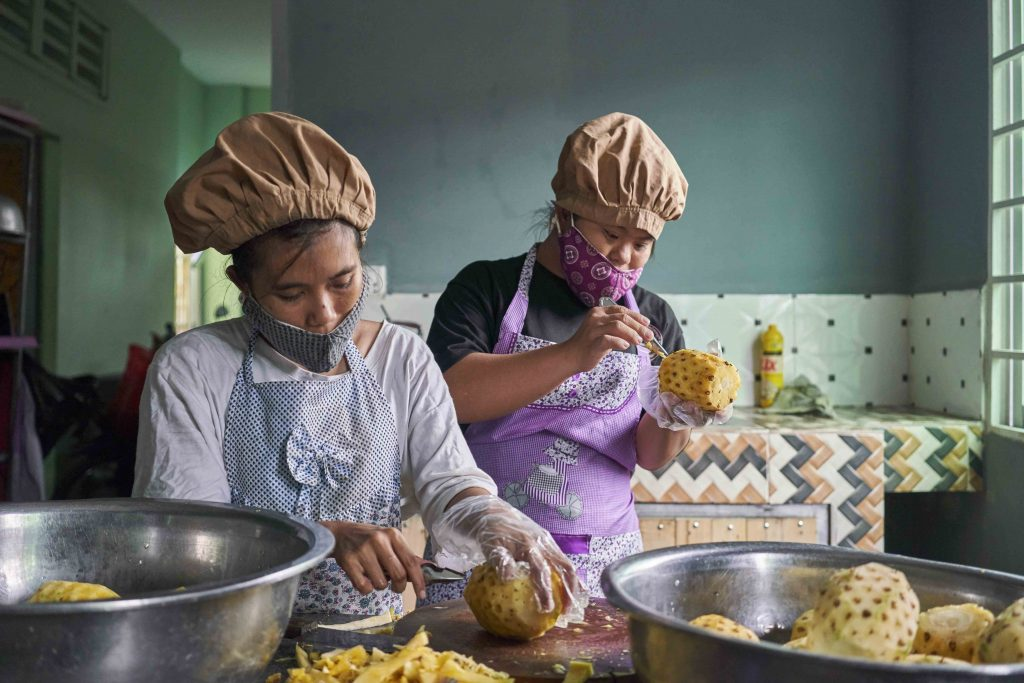 Two women cutting pineapples in a kitchen