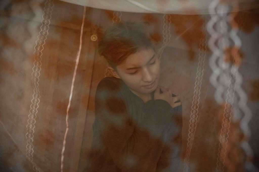 An intimate photo of a Chris, a trans woman from Myanmar, in her bedroom.